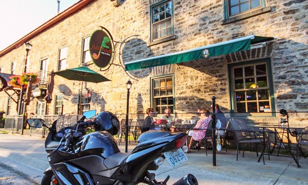 Motorcycle in front of brick building. People sitting on patio