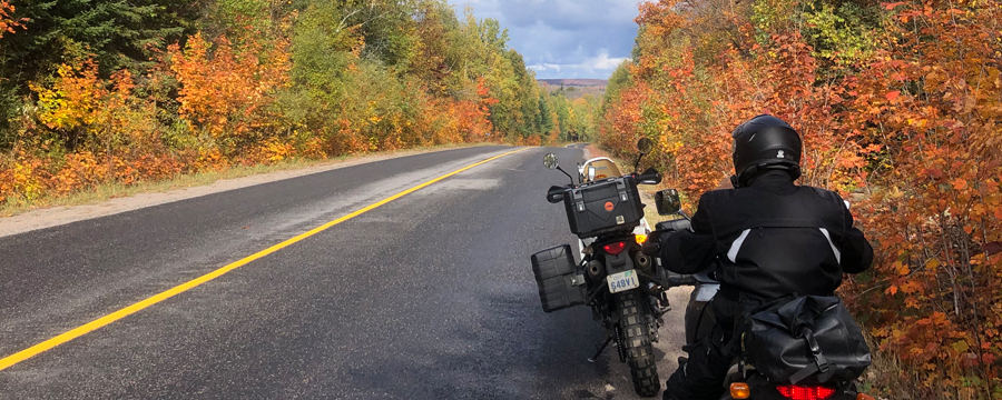 Two motorcycles on side of road with fall colours