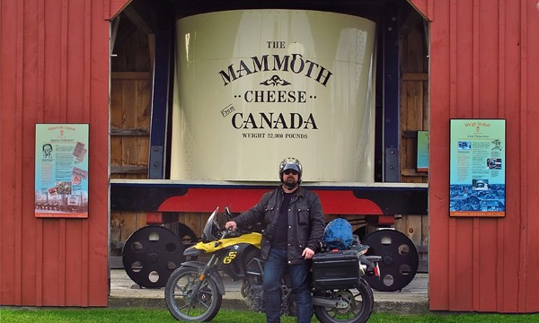 Man with motorcycle standing in front of mammoth cheese monument