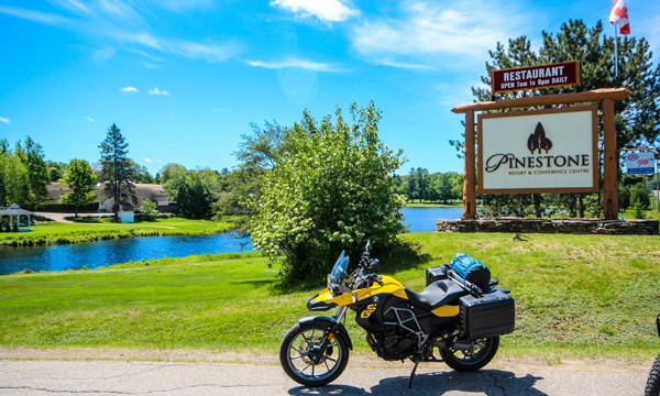 Motorcycle in front Pinestone Resort sign and lake
