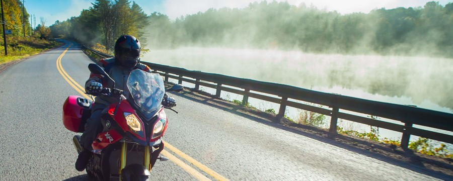 Motorcycle riding past a misty lake.